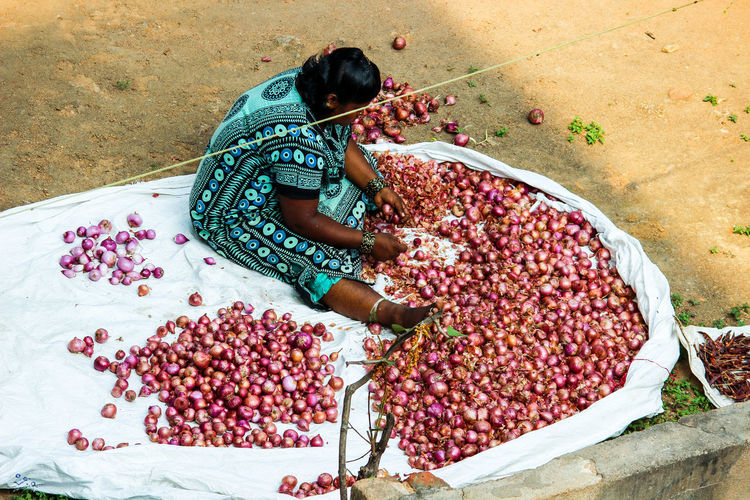 High Angle View Of Woman Cleaning Onions At Market