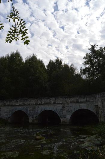 Arch bridge over calm river against cloudy sky