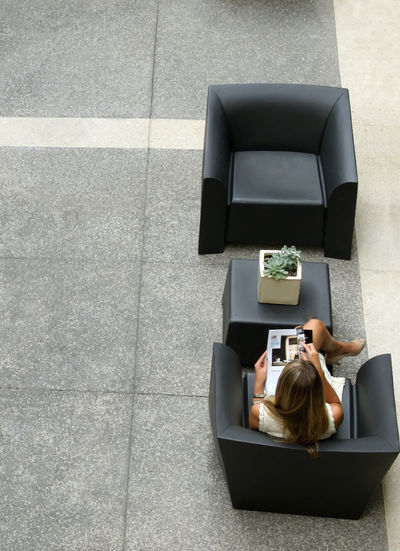 Woman reading in lounge area from above Reading Business Businesswoman Convenience Copy Space Day Full Length High Angle View Lounge One Person One Woman Only One Young Woman Only Relaxation Sitting