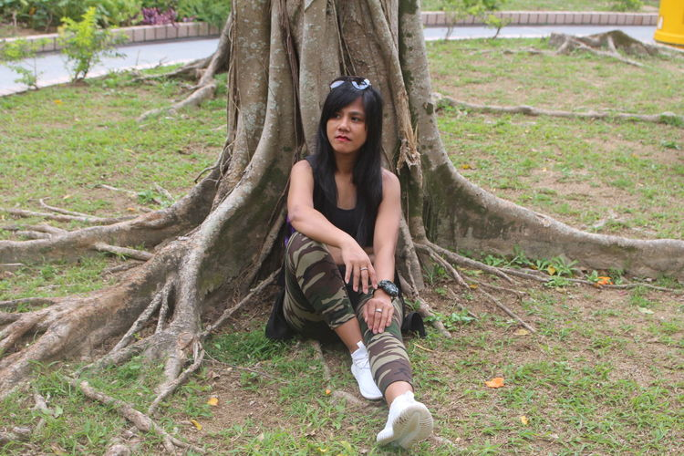 Woman sitting by tree trunk in park