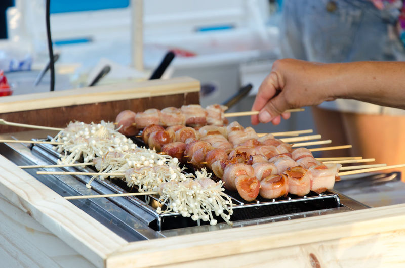 Cropped Hand Of Person Preparing Food On Barbeque Grill