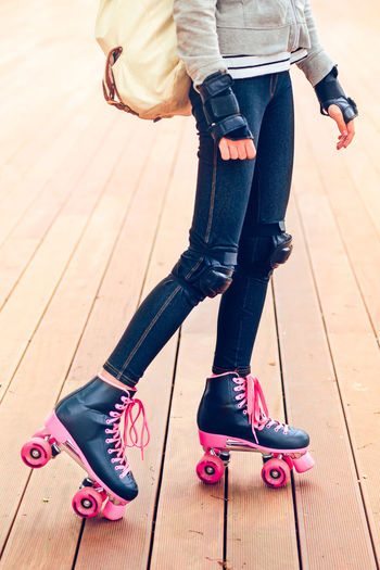 Close up of legs of teenage girl wearing jeans and pink black skates standing on wooden stage Activity Day Denim Faceless Female Girl Girly Jeans Legs Lifestyles Low Section Pink Protective Real People Recreation  Rollerskating Skate Skater Sport Sports Sportswear Teenager Vertical Young Youth
