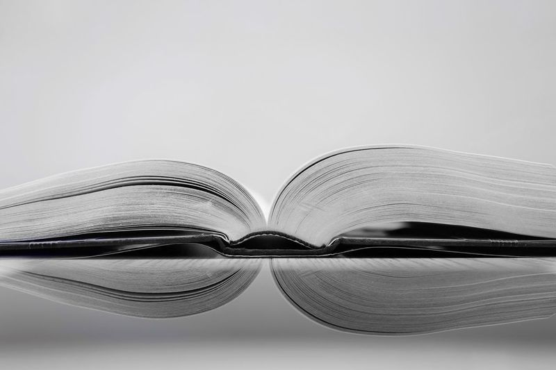 Monochrome The Still Life Photographer - 2018 EyeEm Awards Reading Reading A Book Still Life Photography Still Life Pages Edges Pages Of A Book Pages Page Bookphoto Book Love Books ♥ Books Book Reflection Photography Reflections Close-up Copy Space Studio Shot No People White Background Indoors  Still Life Reflection Transparent Table Focus On Foreground
