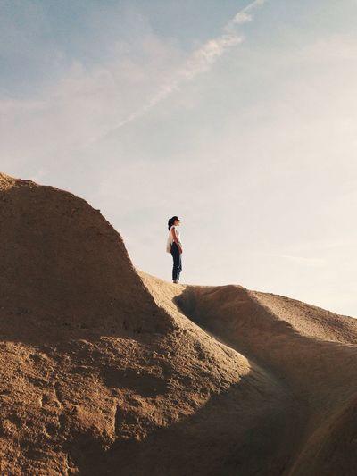 Man standing on sand dune against sky