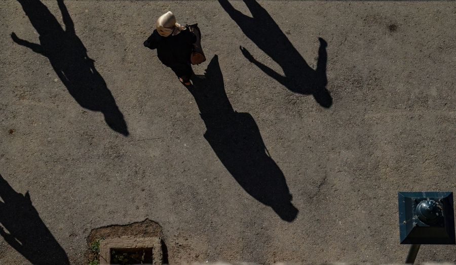 High angle view of woman standing on road during sunny day