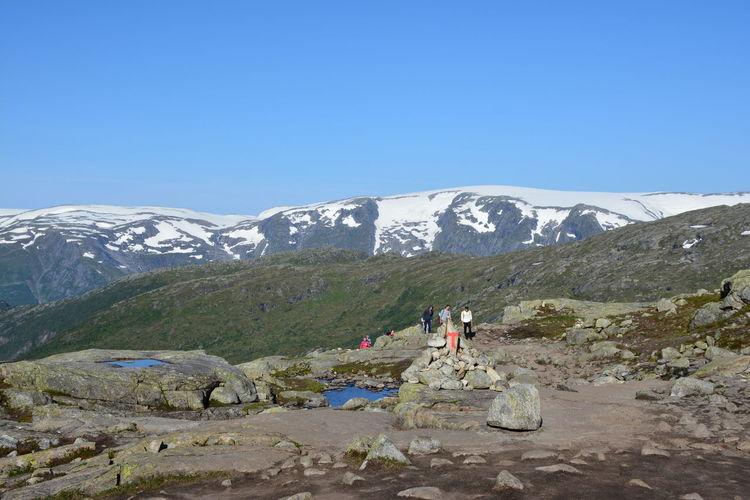 People On Mountain Peak Against Clear Blue Sky