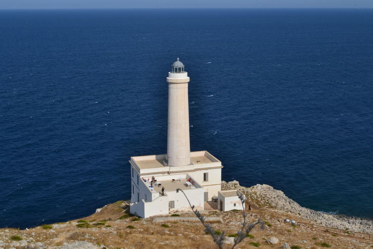 High Angle View Of Lighthouse Next To Sea Against Clear Sky