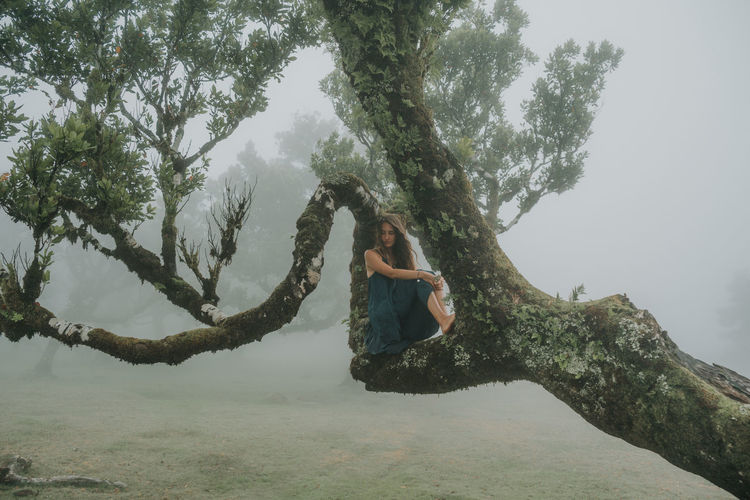 Woman sitting on tree in forest during winter