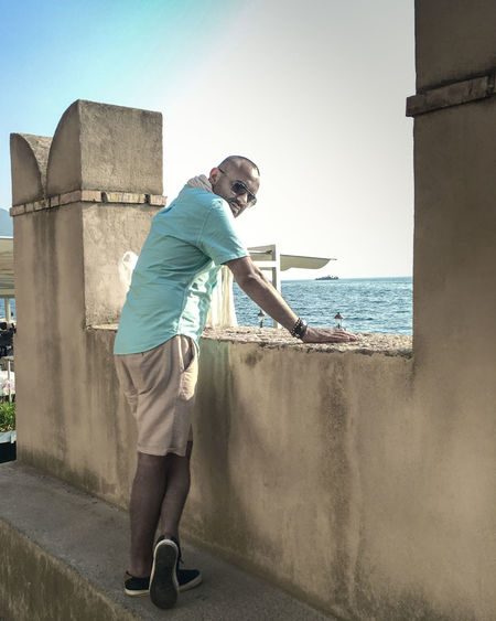 Side view portrait of man standing by retaining wall against sky