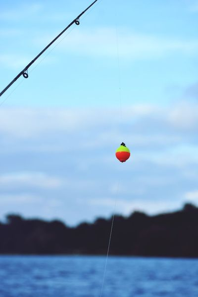 Fishing line Fishing Pole Fishing Line Blue Blue Background Orange Color Fishing Bobber Water Sky Focus On Foreground Hanging Nature No People Beauty In Nature Outdoors Drop Fishing Lake Mid-air Waterfront Scenics - Nature Cloud - Sky