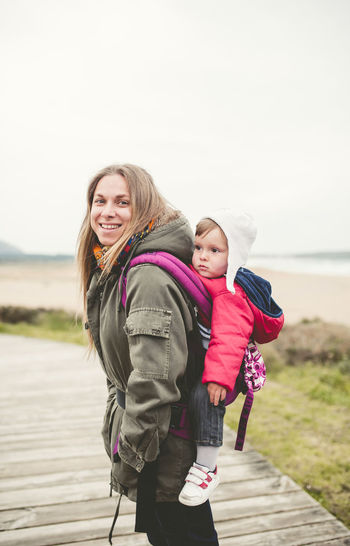 Side view portrait of smiling mother carrying baby boy on boardwalk