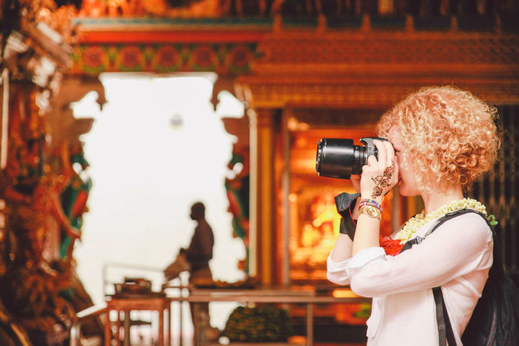 Close-up of woman clicking photograph in temple