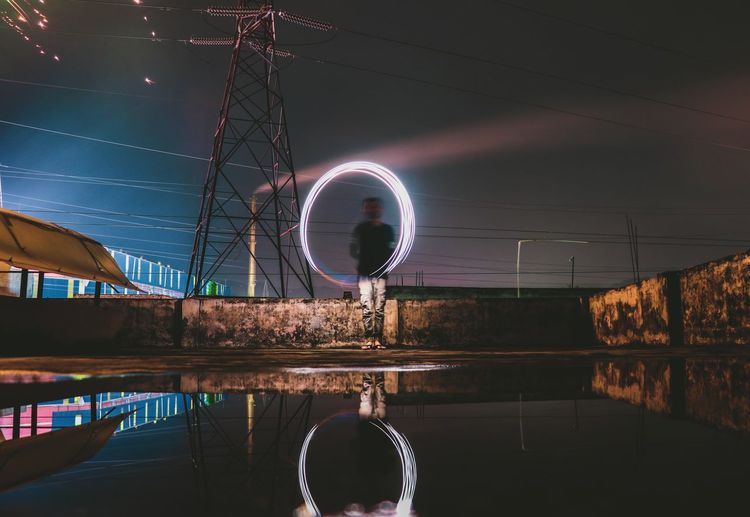 Man with wire wool by water against sky at night