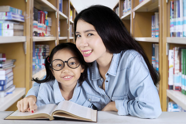 Portrait of mother and daughter with book in library