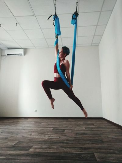 Low angle view of woman hanging on textile while exercising at home