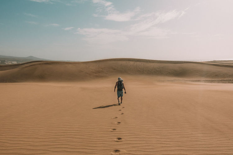 Rear view of man walking on desert against sky