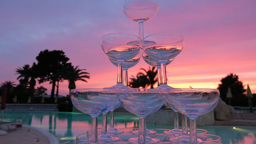 Stack of martini glass on table against sky during sunset