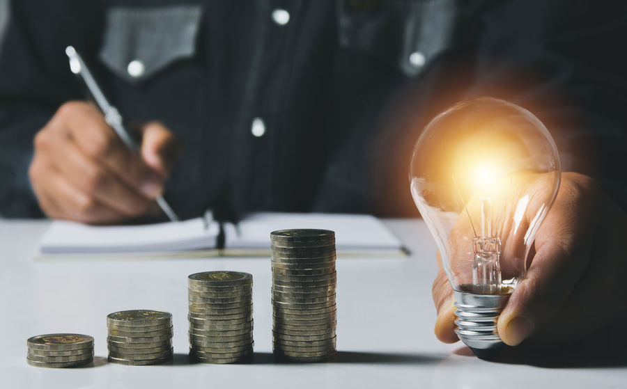 Hand of male holding a light bulb with stack of coins for accounting and creative concept. Finance Business Coin One Person Human Hand Wealth Human Body Part Holding Currency Savings Men Midsection Hand Indoors  Front View Stack Table Focus On Foreground Close-up Counting Finger