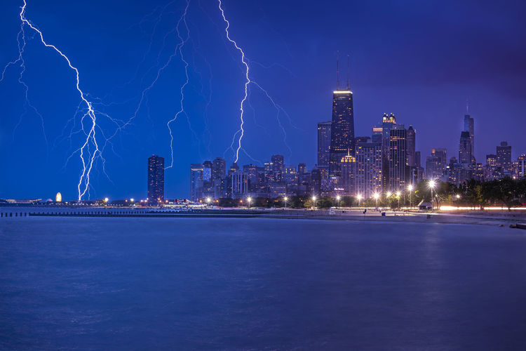 Forked lightning over city by river against sky at night