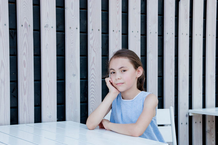 Bangs Boundary Casual Clothing Child Childhood Cute Females Front View Girls Hairstyle Innocence Leisure Activity Lifestyles One Person Portrait Real People Sitting Smiling Women Wood - Material