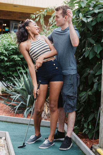 Full length of couple playing miniature golf