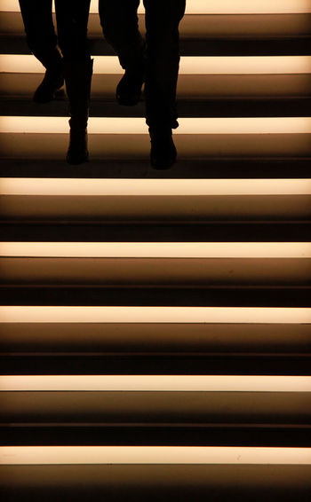 Low Section Of Silhouette People On Illuminated Staircase