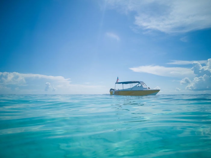 Low angle boat mooring on a turquoise crystal clear water against blue skies.