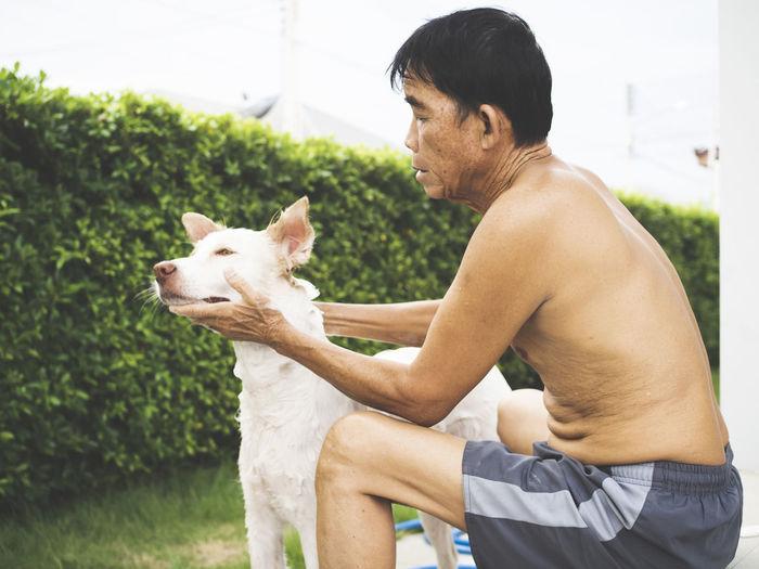 Side view of shirtless man touching dog in back yard