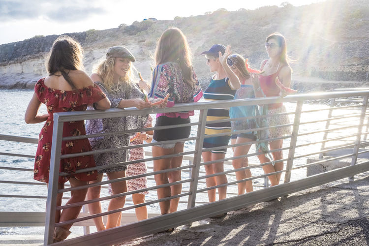 Female friends standing by sea