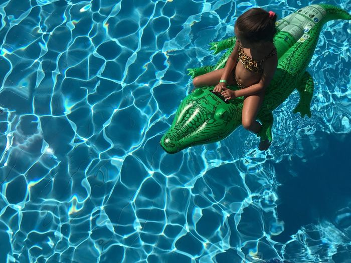 High angle view of girl sitting on inflatable crocodile in swimming pool