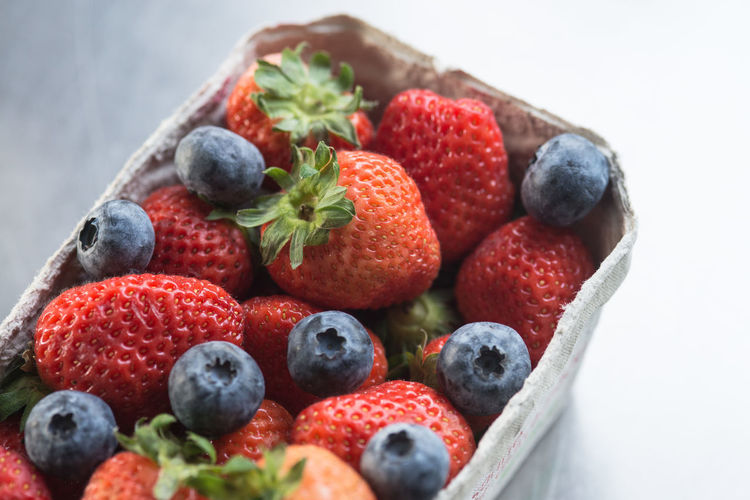 Close-up of strawberries and blueberries in cardboard container