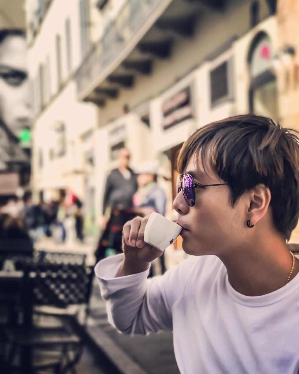 Side View Of Young Man Drinking Coffee At Cafe