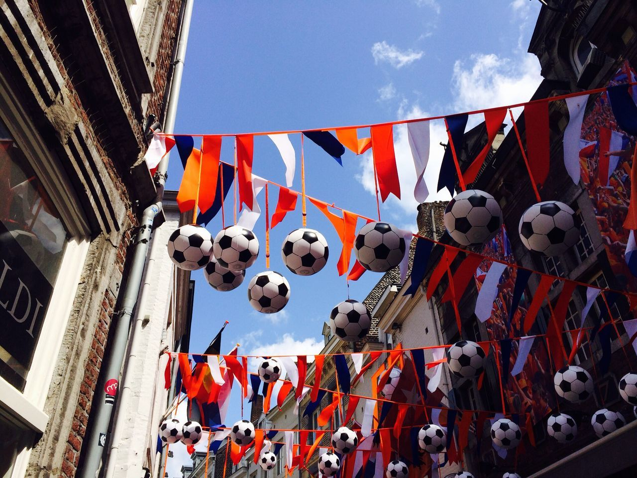 Low angle view of soccer balls hanging from rope against sky