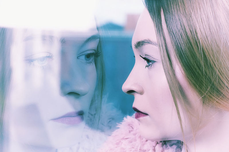 Close-Up Of Young Woman With Reflection On Glass