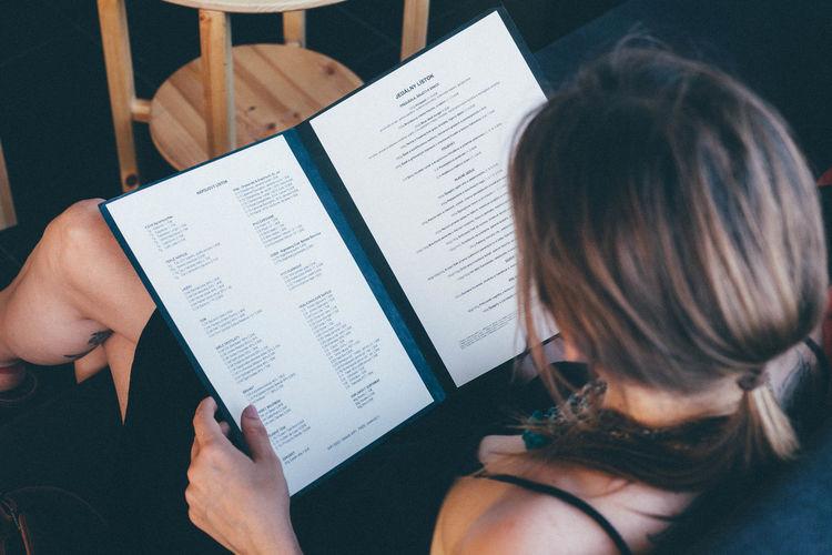 High angle view of woman reading menu at restaurant