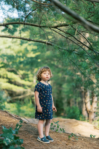 Portrait of a girl standing against trees