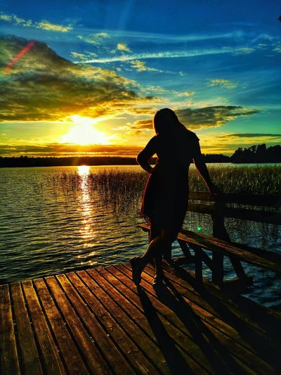 Woman standing on pier over lake against sky during sunset