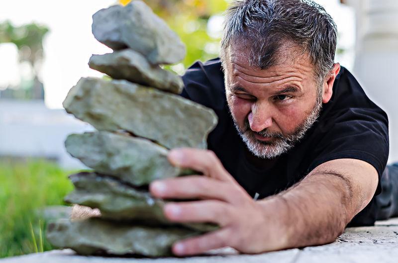 Mature man stacking rocks outdoors