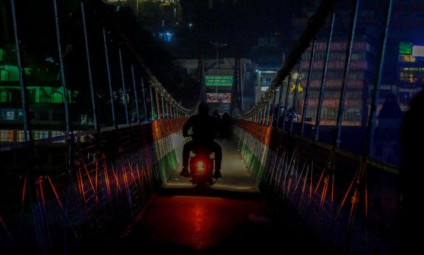 Rear view of man standing on illuminated bridge at night