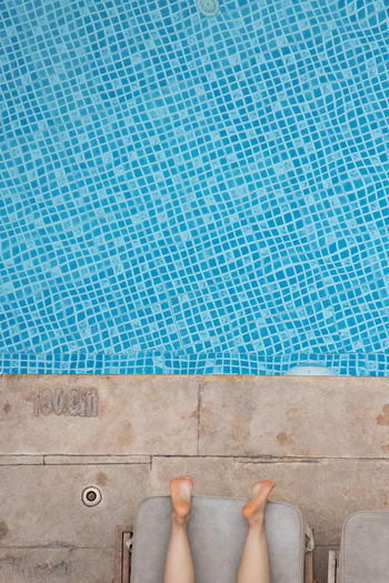 Low section of woman standing by swimming pool