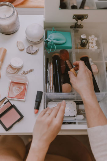 High angle view of woman holding make-up equipment