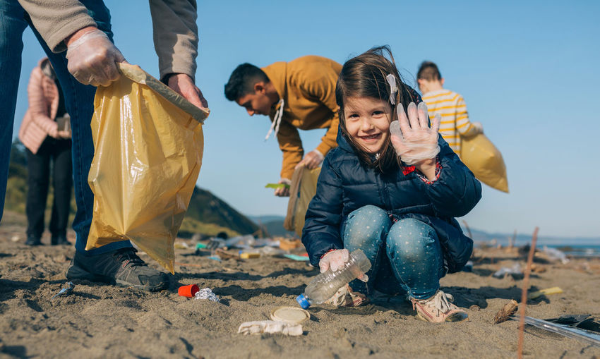 Portrait of cute girl gesturing while picking garbage at beach
