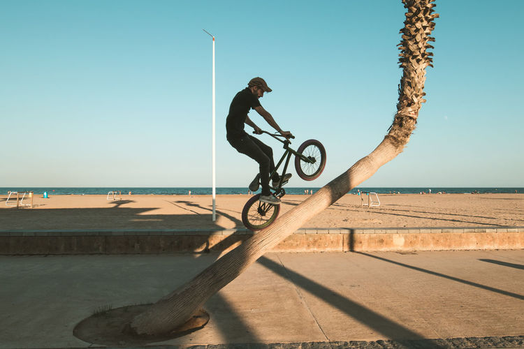 Man riding bicycle by sea against clear sky