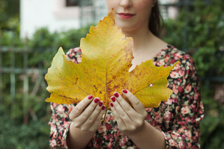 Woman Holding Big Yellow Leaf