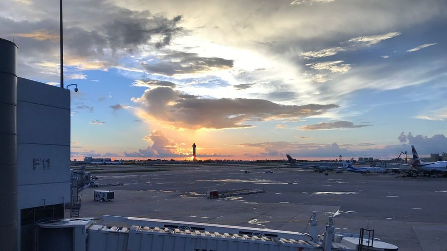 Arrival Departure Board Airport Terminal Airport Runway Airplane Sunrise Yellow Sky Orange Travel Sunset Airport Sunset Cloud - Sky Sky Transportation Sunset Architecture Water City