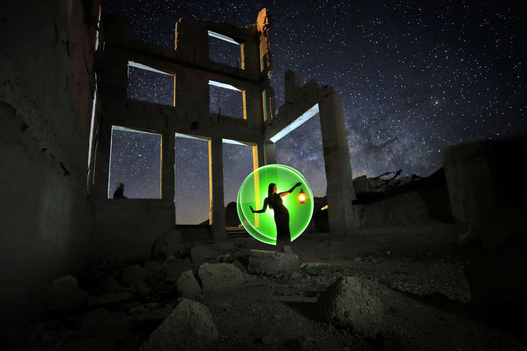 Illuminated lighting equipment on rock by building against sky at night