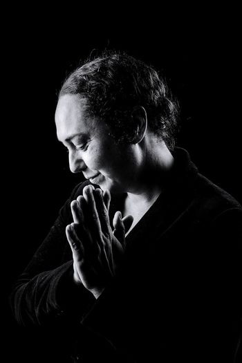 Mature Woman Praying While Standing Against Black Background
