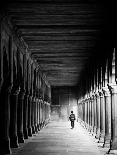 Rear view of woman walking on footpath in old building