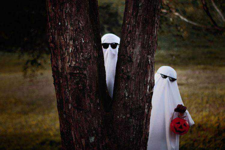 Men wearing halloween costumes hiding behind tree in forest