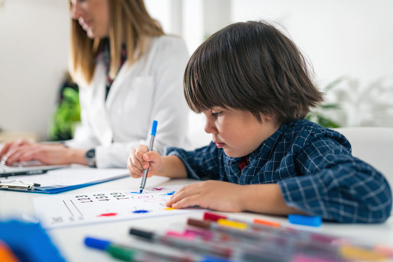 Teacher and student drawing on table in classroom